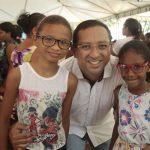 Ricardo Diniz entrega óculos de grau para alunos.